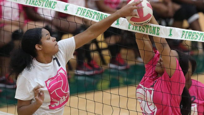Firestone's Si'Ayera Boone is blocked by Buchtel's TyRae'ah Varner during a volleyball game Oct. 3, 2019, at Firestone High School in Akron.