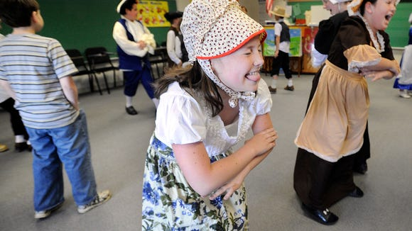 Stewartstown Elementary School 4th grader Victoria Johnson has a hard time keeping a straight face while dancing in music class during Friday's Colonial Day celebration at the school.