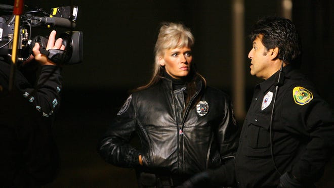 MPD officer Jami Brown talks with Erik Estrada during the filming of the CBS show Armed and Famous. Brown was Estrada's partner for the duration of the show. Chris Bergin/ The Star Press