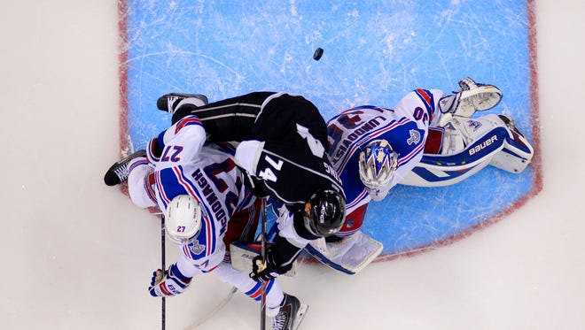 The puck goes into the net as Los Angeles' Dwight King, middle, falls on Rangers goalie Henrik Lundqvist under pressure from defenseman Ryan McDonagh, left, during the third period of Game 2 in the Stanley Cup Final on Saturday night.