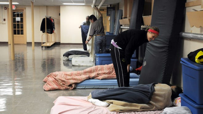 UW-Oshkosh student worker Adriene Barman woke up a client at Day By Day Warming Shelter last winter. Cold temperatures have put the overnight shelter at capacity.