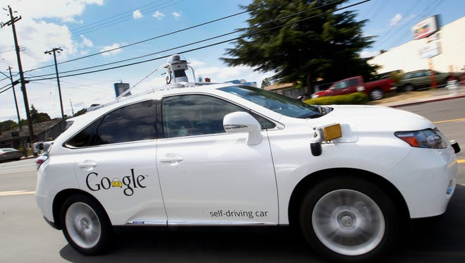 Google's self-driving Lexus car motors along a street during a demonstration at the Google campus in Mountain View, Calif.