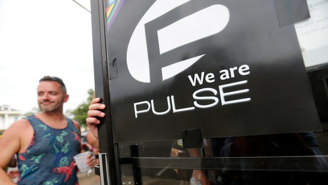 "A sign with the logo of the Pulse nightclub hangs on the entrance as revelers for ""New Orleans Pride"" festivities enter Mags 940 Bar in New Orleans, Saturday, June 18, 2016."
