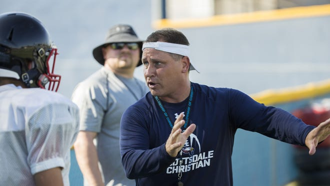 Scottsdale Christian Academy's head coach Chuck Gibbs shows the team how to go through a drill during a practice at Scottsdale Christian Academy on August 8, 2016 in Scottsdale, Ariz.