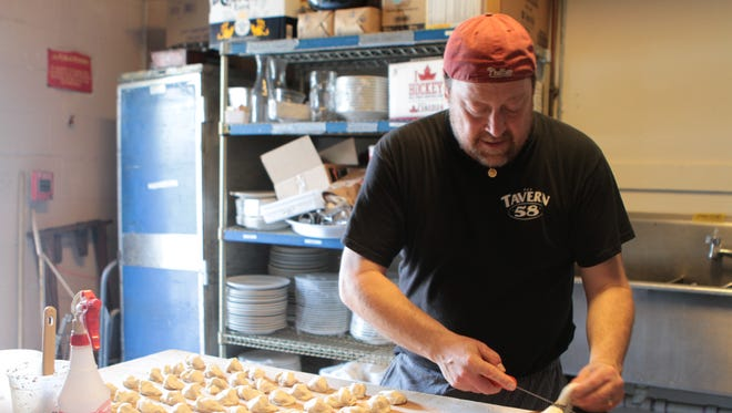 Mike Schnupp, executive chef at Tavern58 at Gibbs, prepares dinner rolls at the restaurant.