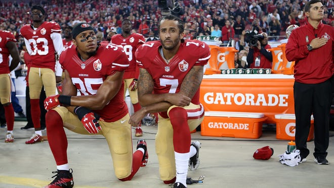 San Francisco 49ers Eric Reid (35) and Colin Kaepernick (7) take a knee during the National Anthem prior to their season opener against the Los Angeles Rams during an NFL football game Monday in Santa Clara, CA.