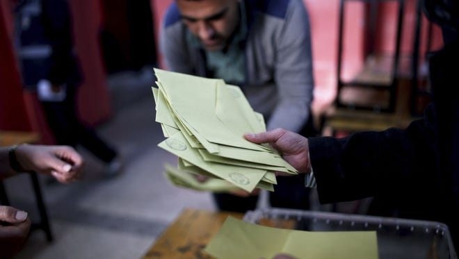 Members of an electoral committee take part in a counting procedure after the closing of the voting inside a polling station in Diyarbakir, southeastern Turkey, on Sunday, April 16, 2017.