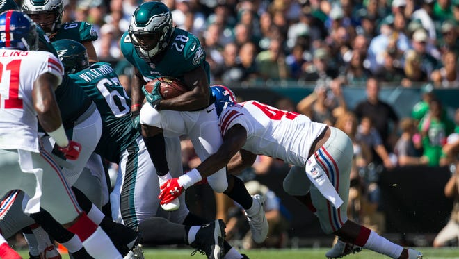 Eagles running back Wendell Smallwood tries to hurdle through the New York defense during a recent game. He's one of five running backs on the Eagles' 53-man roster with the acquisition of Jay Ajayi.