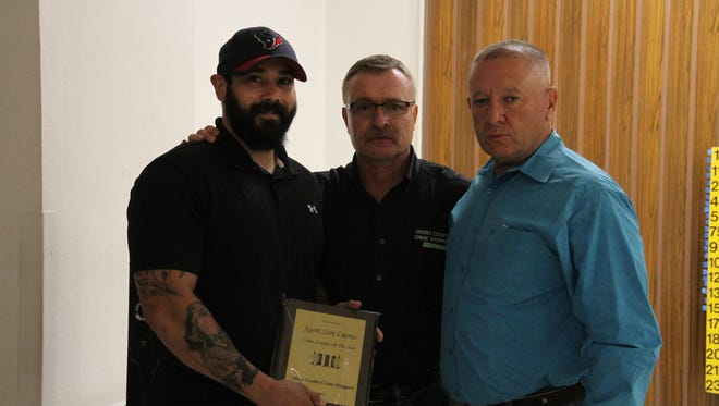 Otero County Sheriff's Office narcotics agent Sam Lueras was named Crime Stopper of the Year Saturday. Lueras (L) is presented with the award by T.O. Livingston (M) and Sheriff Benny House (L).