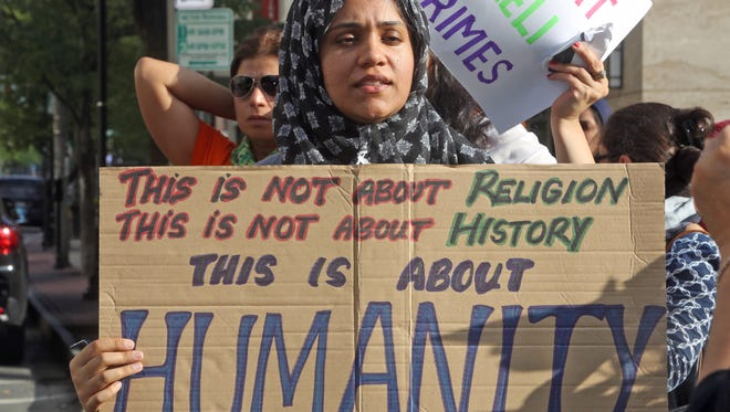 Mahreen Rashid of Hartsdale holds a sign as she takes part in a Gaza solidarity rally in White Plains Aug. 4, 2014. Dozens of people from WESPAC, Jewish Voice for Peace-Westchester, and Concerned Families of Westchester gathered.