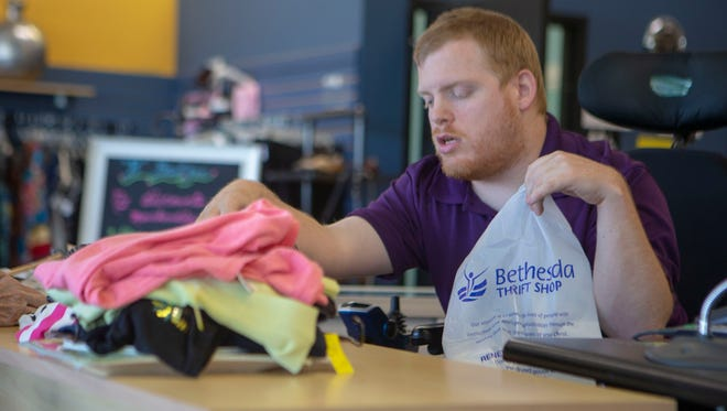 Adam Voisin rings up a customer at the Bethesda Thrift Store in Hales Corners.