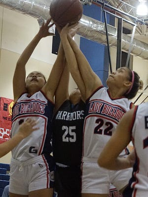 Okkodo senior Alannah Crame, right, fights for one of her 10 rebounds in the Bulldogs 43-31 IIAAG Girls' Basketball League win against the St. Paul Warriors at Okkodo on Tuesday, Dec. 1.