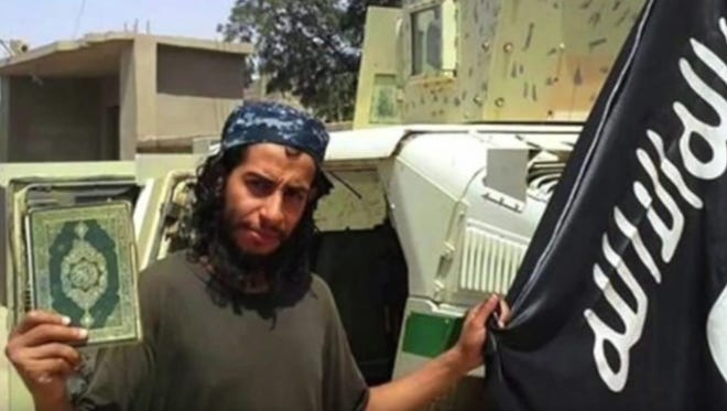 A framegrab made from an undated video released by the jihadist group calling itself Islamic State shows Abdelhamid Abaaoud posing with a Quran and the Islamic State flag at an undisclosed location.