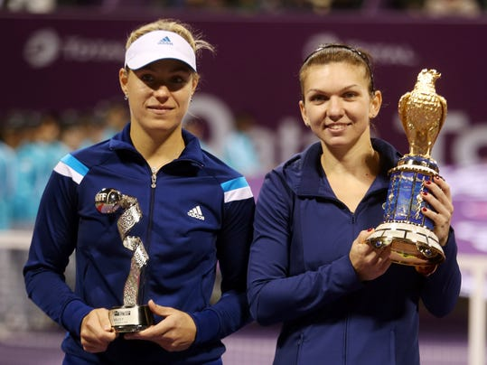 Simona Halep of Romania, right, and Angelique Kerber of Germany pose with their trophies after the final match of Qatar WTA Ladies Open tennis tournament, in Doha, Qatar, Sunday, Feb. 16, 2014. (AP Photo/Osama Faisal)
