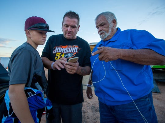 "Race car driver Aasa ""Boo"" Flores, left, his father Larry Flores and grandfather Lawrence Flores prepare for a race at the Southern New Mexico Speedway."