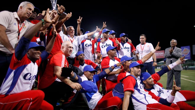 Cuba players pose for photos with the Caribbean Series trophy after defeating Mexico.