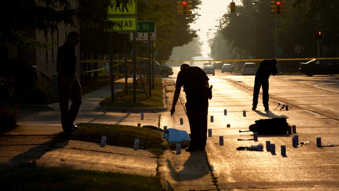 Members of the Port Huron Police Department investigate the scene of a suspected hit-and-run Sept. 2, 2015, on Oak Street between 10th and and 11th Streets in Port Huron.