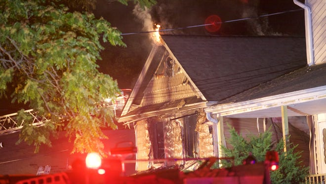 Flames leaped from the eaves of a home in Belmar in a fire that left two dead Monday.