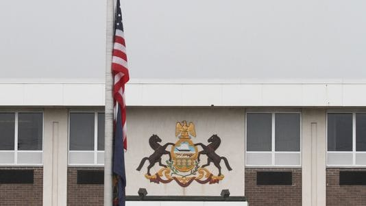 The U.S. flag is flown at half-staff outside of the Pennsylvania State Police headquarters in Dunmore, Pa., on Sept 13, 2014. A late-night ambush outside a state police barracks in Pennsylvania's rural northeastern corner left one trooper dead and another critically wounded, and authorities scoured the densely wooded countryside and beyond on Saturday looking for the shooter or shooters.