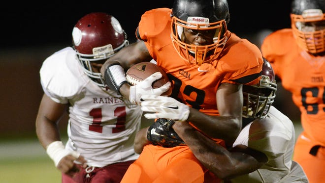 Cocoa's Justin Weaver (23) tries to run through the tackle of Raines players Jermaine Oliver (11) and Michael Pinckney (8) during Friday's game at Cocoa Stadium.
