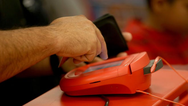 A customer uses the credit card scanner at a Target store on Dec. 19.