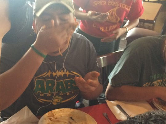 Winner Jose Cuevas of Coachella Valley High finishes off his plate during the Spicy Thai Noodle Challenge on Saturday at My Thai restaurant.