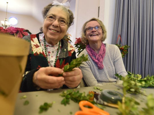 """Hedy Heise, left, and Gunilla Wilson create holiday wreaths during last year's ADVENTure at Ephraim Moravian Church, part of the village's """"Christmas in the Village"""" celebration"""