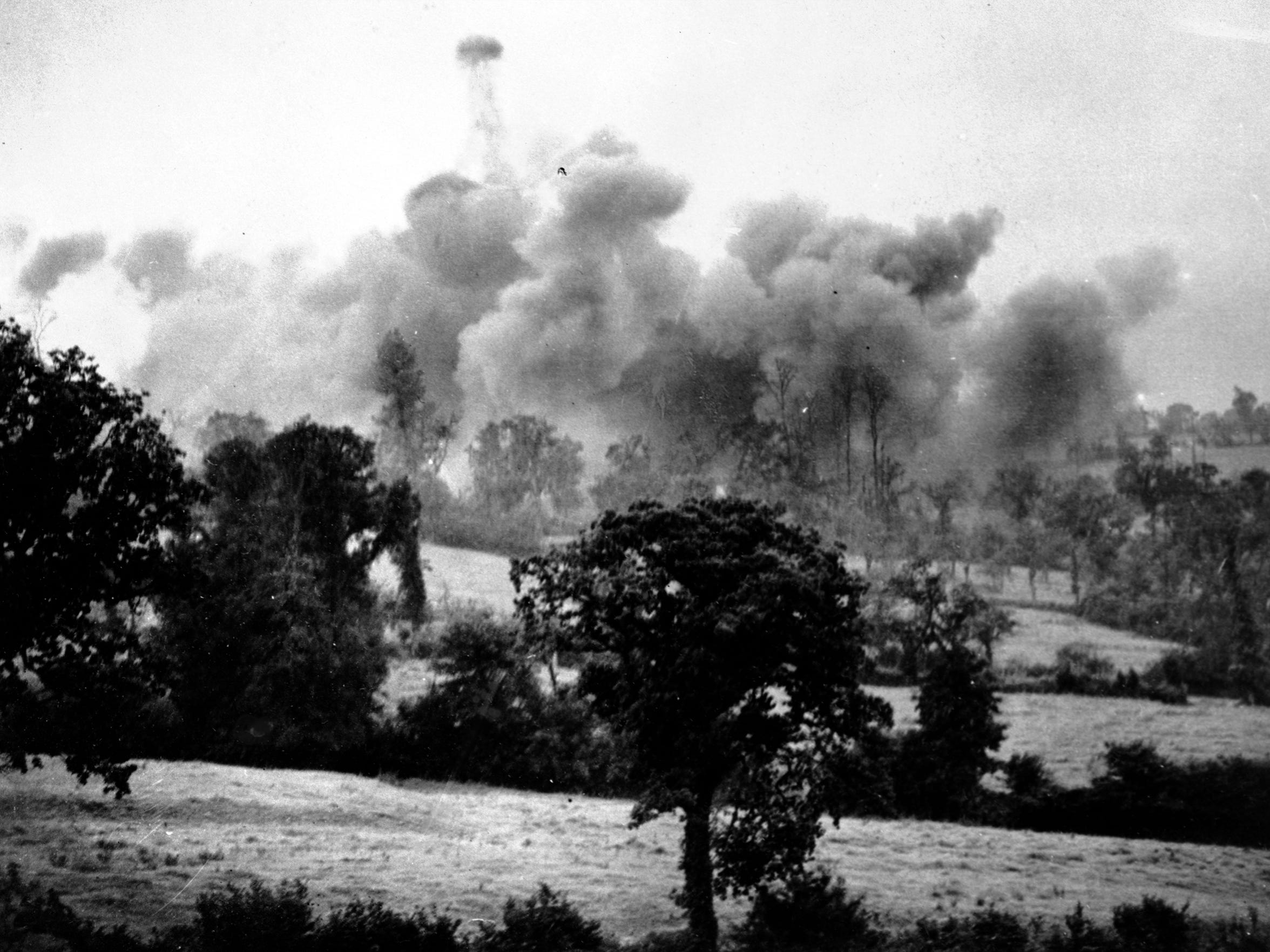 Thousand pound bombs explode near German lines during tha launch of a new American offensive in the St. Lo sector of France, July 26, 1944. This was the last picture taken by Associated Press war photographer, G. Bede Irvin, before he was killed by a bomb fragment. The film pack containing this picture was the only part of Irvin's equipment left intact by the bomb explosion and was sent from the front by a fellow photographer.