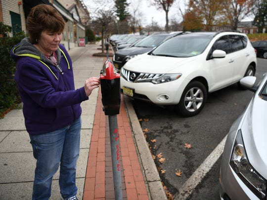 Kathleen Mulvihill of Saddle Brook paying the meter after pulling into parking spot No. 24 in downtown Ridgewood on Saturday.