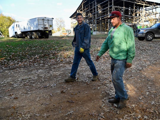 Brothers Erick, left and Jhony Aguila walk back to the bunkhouse, where at one time they both lived on the Hancock farm in Bumpus Mills, Tenn., Tuesday, Oct. 24, 2017.