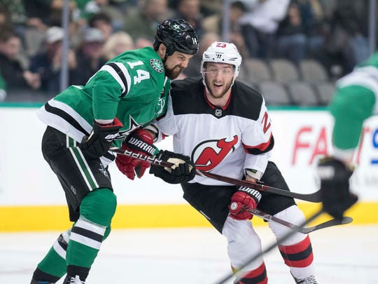Jan 4, 2018; Dallas, TX, USA; Dallas Stars left wing Jamie Benn (14) New Jersey Devils right wing Stefan Noesen (23) fight for the puck during the first period at the American Airlines Center.