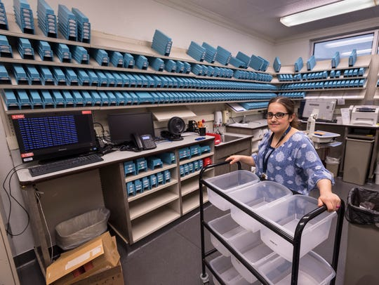 Pharmacy Director Stephanie Aflague stands with empty bins for about 2,000 medicines typically in stock at Tulare Regional Medical Center.