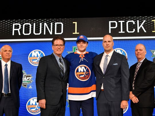 Jun 22, 2018; Dallas, TX, USA; Noah Dobson, center, poses for a photo with team representatives and new GM Lou Lamoriello, far left, after being selected as the number twelve overall pick to the New York Islanders in the first round of the 2018 NHL Draft at American Airlines Center.