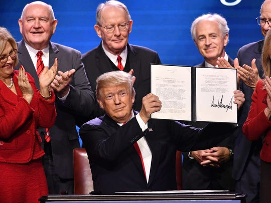 Jan. 8, 2018: President Donald Trump, front center, holds an executive order he just signed on rural broadband. He is flanked by Rep. Diane Black, left, Agriculture Secretary Sonny Perdue, Sen. Lamar Alexander, Sen. Bob Corker, Sen. Pat Roberts and Rep. Marsha Blackburn at Gaylord Opryland Resort & Convention Center in Nashville.