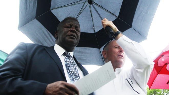 Worshippers shelter beneath an umbrella Sunday as a light drizzle fell during a unity prayer service hosted among various churches. Faith leaders prayed for divine guidance for the community, which has been troubled recently by much violence. More than three dozen people attended the prayer event in Frenchtown.