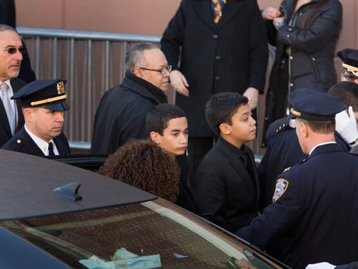 Jaden Ramos, center, arrives at the funeral for his