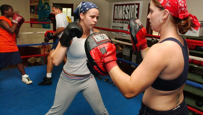 Ashley Walus, left, works out with the punching mitts with Amy Swope at the Staunton Boxing Club.