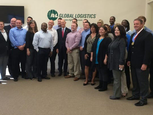 Gov. Rick Scott (center) joined employees of R+L Global Logistics on Monday.