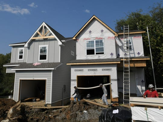 Construction crews work on a pair of homes in East