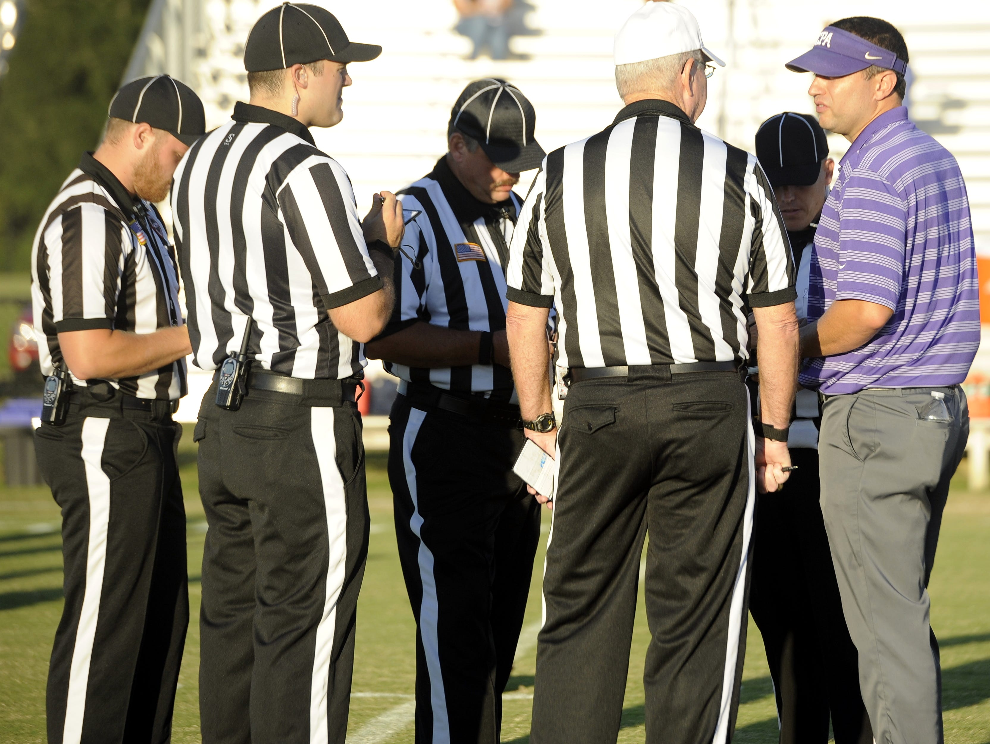 Christ Presbyterian Academy football coach Ingle Martin talks with North Middle Football Officials Association referee Jody Swearingen (white cap) prior to the game with White House Heritage on Sept. 2, 2016.