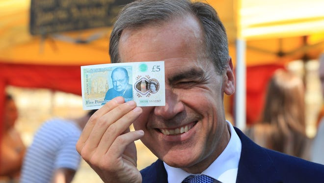Bank of England Governor Mark Carney holds a new plastic £5 note as he visits Whitecross Street market in London, Tuesday, Sept. 13, 2016. The polymer note is said by the Bank of England to be cleaner, safer and stronger than paper notes, lasting around five years longer.