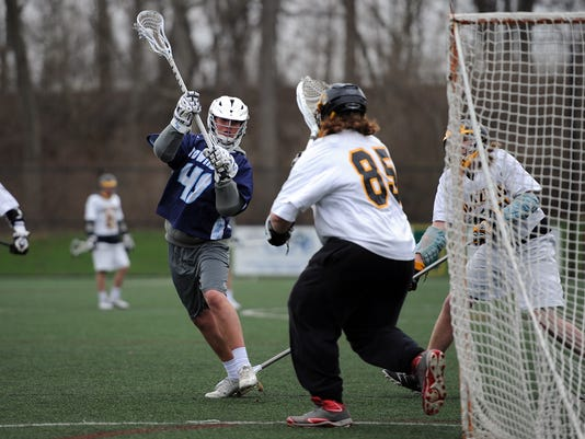 Manheim Township's Hogan Glick releases a shot in front of Lancaster Mennonite's Ivo Colon at Lancaster Mennonite High School on Wednesday, April 8, 2015. The Blue Streaks won 20-4. Patrick Blain For GameTimePA.com