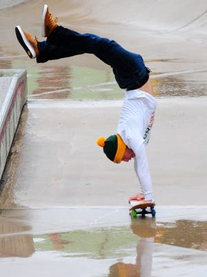 Ryan Baldwin of Cambridge, Minn., does a handstand trick during the 5th annual Going Big in the Bay skateboard competition and fundraiser at Joannes Sk8 Park in Green Bay on Saturday, October 4, 2014.