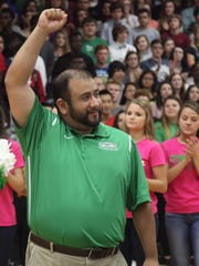 Fort Myers High School girls assistant basketball coach Arthur Cedeno waves to fans during a pep rally to honor the state champion Green Wave. He has taken a position as head coach at Lehigh Senior High.