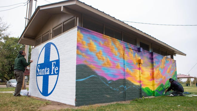 What once was a beige restroom at Santa Fe Park, 1500 N.E. Division St., is transformed into a colorful urban art project thanks to Jamie Colon, left, Robert Tapley Bustamante, right, and Andy Valdivia, not pictured. On Thursday, the three artists met to continue work on their designated sections.