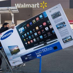 Black Friday shopper Umer Gonzalez pushes his Samsung big screen TV after purchasing it at a Walmart in Fairfax, Virginia, on November 28, 2014.