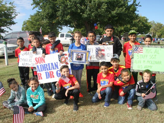 Torque Football Club kids hold signs of family members