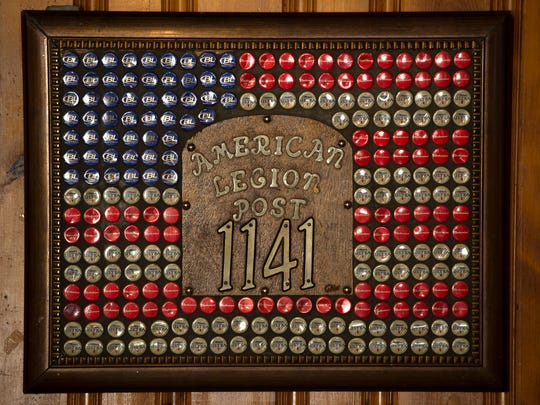 A framed American flag Ð created with Bud Light, Budweiser and Michelob Ultra bottle caps Ð adorns a post at the American Legion Post 1141 in New Haven, Ill.