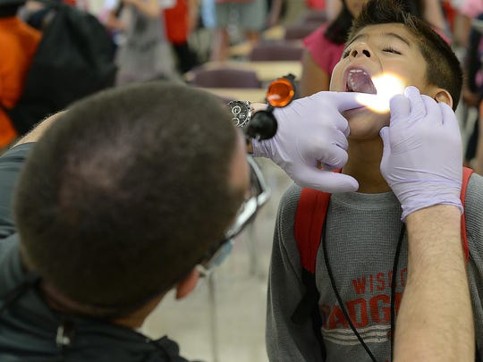 Dentist Patrick Maraka, left, screens Brando Martinez Hernandez for dental issues at the annual Back to School Store at Green Bay East High School.