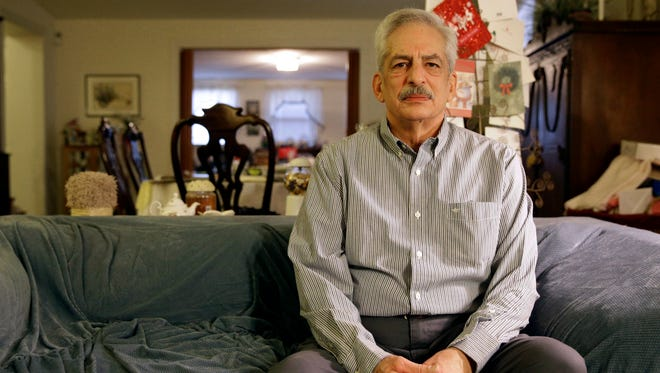 Stan Osnowitz poses in his living room in Baltimore on Jan. 10. Osnowitz, 67, lost his state unemployment benefits of $430 a week in December. The money put gasoline in his car so he could look for work.